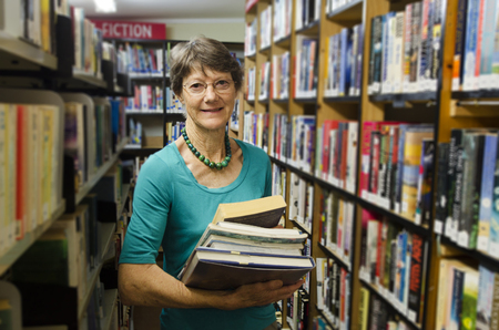 A woman librarian holds books beside bookshelf in library.