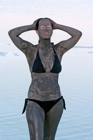 sourced: A young woman in a bathing suit is enjoying the natural mineral mud sourced from the Dead Sea,  Israel.