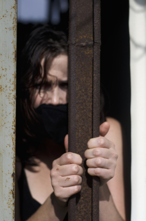 woman prison: A woman trapped in a prison jail cell with a mouth cover Stock Photo