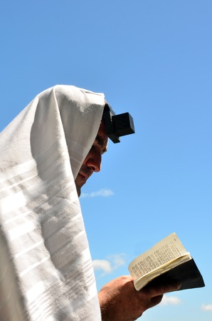 siddur: Jewish man wearing Tallit and Tefillin read from the Torah book, pray to God under a blue sky on Jewish holiday.