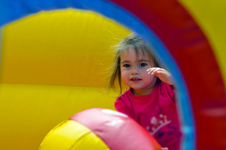 Happy child girl jumps on a children's bouncy castle inflatable jumper playground. Stock Photo