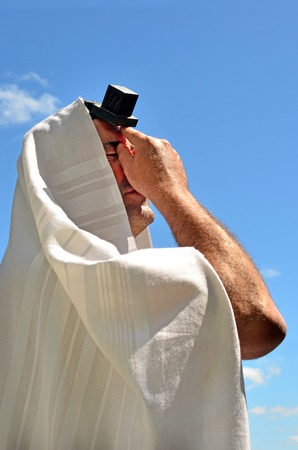 Jewish man wearing Tallit and Tefillin pray to God under the blue sky on Jewish holiday.