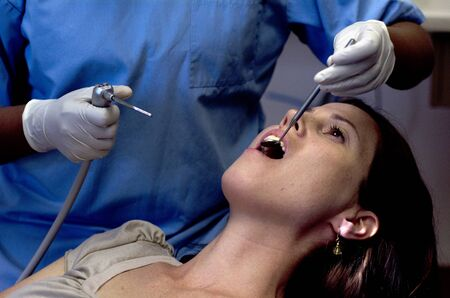 examined: Female patient having her teeth examined by specialist dentist. Stock Photo