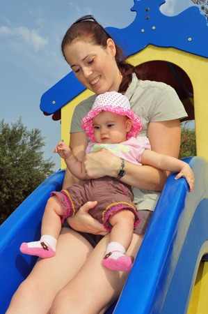six month old: A little six month old baby girl plays with her mom in a playground