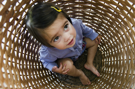 school teens: Scared child hides in a laundry basket. Stock Photo
