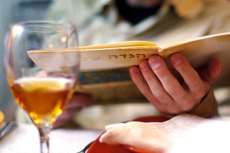 kiddush: Man reads in the Haggadah book during Passover Seder dinner.