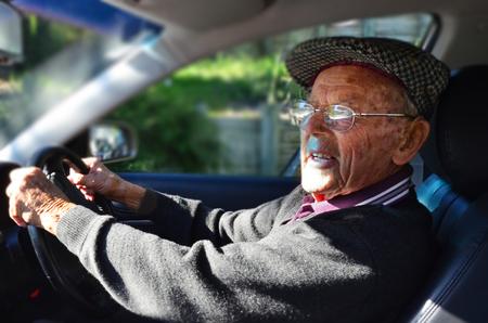 Een zeer oude man met een geldig rijbewijs rijdt in een auto. Stockfoto