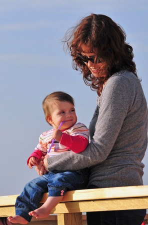 6 month old: Mother holds her baby 6 month old child and smiles.