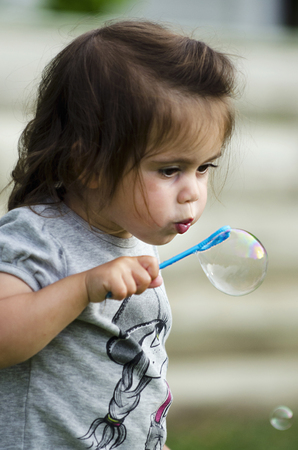 innocent: Portrait of funny lovely little girl blowing soap bubbles.