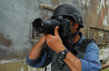 bullet camera: A press photojournalist is holding a camera with a zoom lens and is photographing war and conflict. Stock Photo