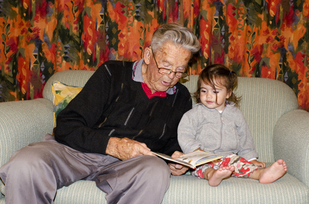 grandad: Great Grandad reads a book to his great grandchild on a coach.