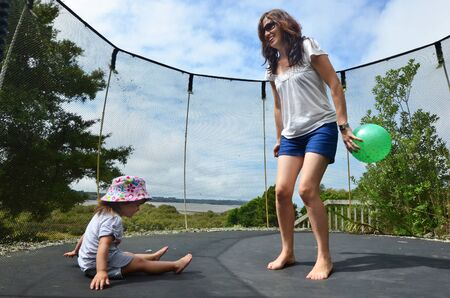 Young Mother and her baby jumping together on a trampoline.