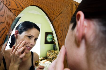 fair complexion: A young caucasian woman looks in the mirror and applies makeup foundation. Stock Photo