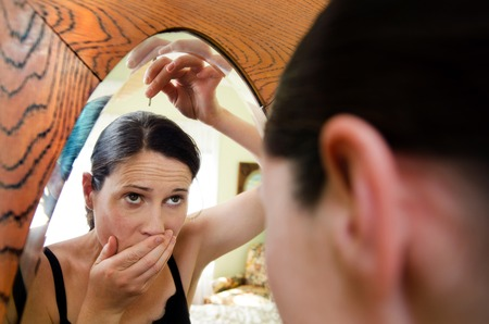 fair complexion: Young caucasian woman looks in the mirror and plucks a grey hair from her head. .