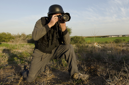 photojournalist: A male press photographer wears a protective helmet and vest and takes photos with a professional camera Stock Photo