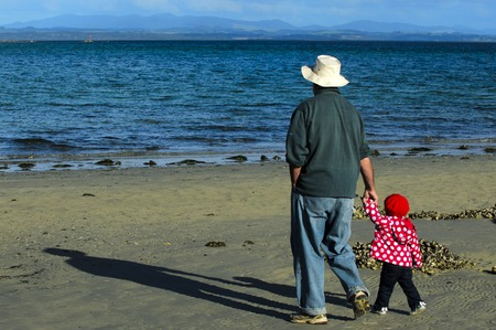 feel affection: Grandfather with granddaughter walks on the beach during winter.