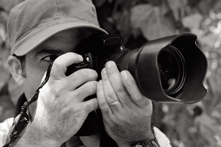 documenting: Nature and Wildlife Photographer looks through a camera outdoor. Stock Photo
