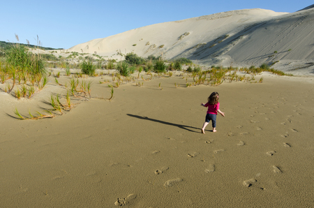 quicksand: Little girl runs over Te Paki sand dunes in Northland New Zealand.