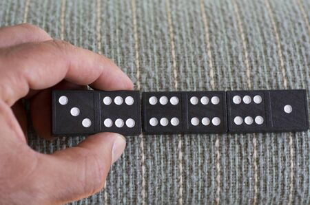 consequence: Mans hand play Domino game. Stock Photo