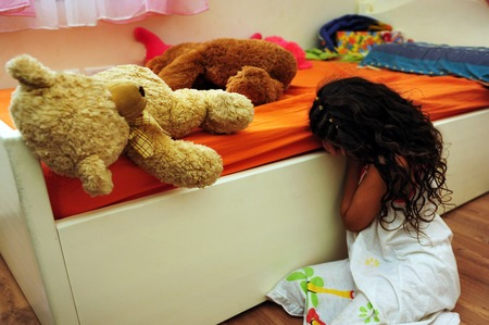 Abused child sitting on the floor in her bedroom, suffering from a severe depression. Banque d'images