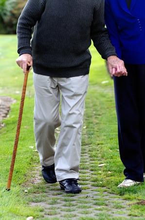 elderly adults: An old couple walk in a street.