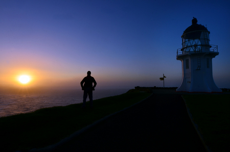 reinga: A man looks at the sunset in Cape Reinga Lighthouse at the edge of the northland, New Zealand. Stock Photo