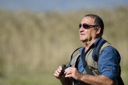 bird watcher: A senior hiker and bird watcher is searching for birds with binoculars.