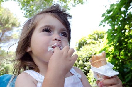 hot summer: Little girl eats Ice cream in a hot summer day. Foto de archivo