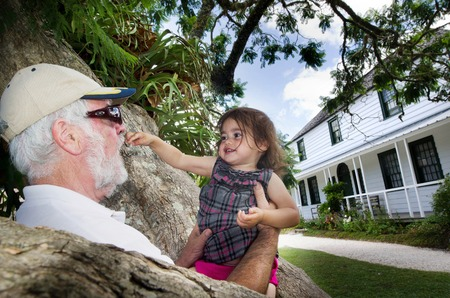 grandchild: Grandfather plays with his little grandchild out side the house.