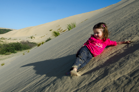 quicksand: Little girl rolled down the slope of snow-white Te Paki sand dunes in Northland New Zealand. Stock Photo