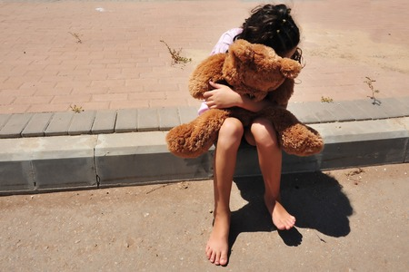 cuddles: A young girl who is a victim of domestic violence walks a street alone and cuddles her teddy bear Stock Photo