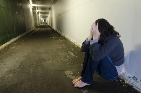Crime scene concept photo of rape victim. A sad woman sits on the floor of a dark tunnel. Stock Photo