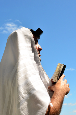 tefillin: Jewish man wearing Tallit and Tefillin read from the Torah book, pray to God under a blue sky on Jewish holiday.