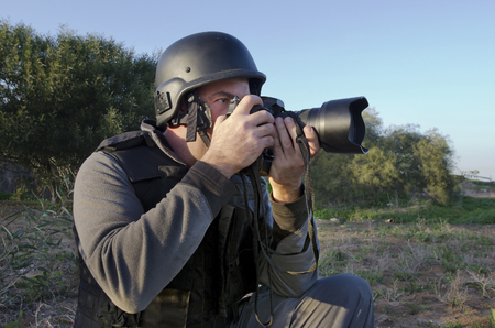 bullet proof: A male press photographer wears a protective helmet and vest and takes photos with a professional camera Stock Photo