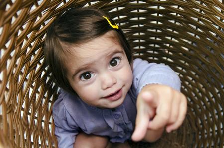 peek a boo: Happy little girl playing peekaboo and hides inside a basket.
