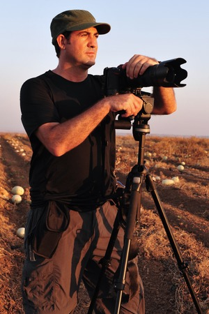 documenting: A photographer is standing and looking at the landscape of a field near a camera on a tripod with a zoom lens to photograph wildlife and nature.