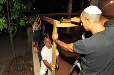 tabernacles: Israeli Jewish family celebrating the Jewish holiday of Sukkoth by building a sukkah.
