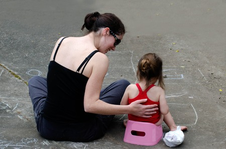 piss: A young mother trains her daughter to use the potty outdoor.