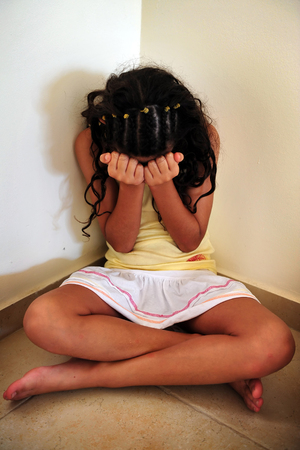 fear child: A young girl who is a victim of domestic violence hides and cries in a corner of her house Stock Photo