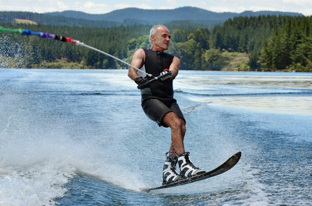 water skier: A water skier in his 60s preforming water skiing sport on a lake. Stock Photo