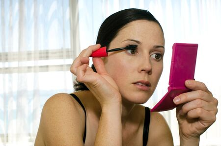health fair: A young caucasian woman looks in mirror and applies mascara makeup. Stock Photo