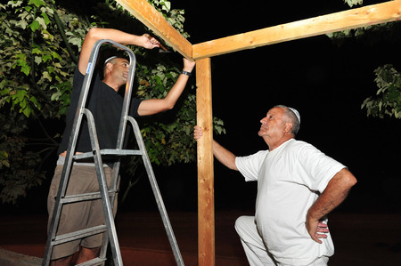 succos: An Israeli men are building a sukka a moments after Yum Kippur was finished.