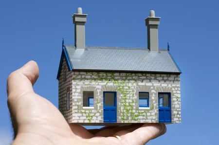 housing industry: Mans hand hold a toy house against blue sky. Concept photo of Real estate market bubble , booming, money,price, rent, grid, home, house, housing, industry and subprime mortgage crisis. (Copy Space).