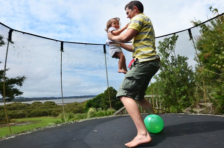 realtionship: Father and his baby jumping together on a trampoline. Stock Photo