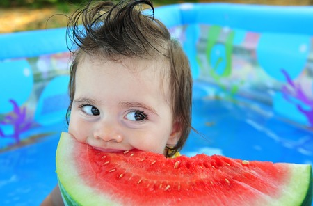 hotter: A baby girl eats a cold watermelon in a baby pool in a very hot day.