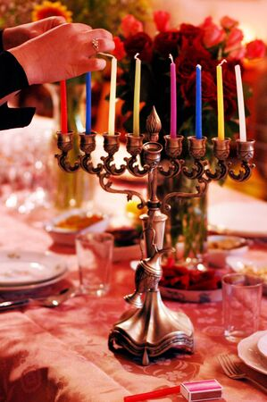 hanukah: Hands of a woman is lighting a candle for the Jewish holiday of Hanukkah that is observed for eight nights and days. Stock Photo