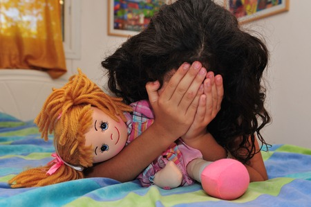 cries: A young girl hides her face and cries on her bed in her bedroom.