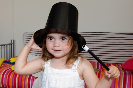 illusionist: Adorable Little magician girl dress of illusionist with hat, holds a wand stick and plays in her bedroom. Stock Photo