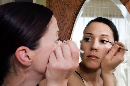 health fair: A young caucasian woman looks in the mirror and applies eyeliner makeup. .