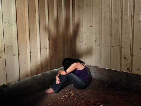 adult rape: A woman who is a victim of abuse is hiding in the darkness of an old shed, sitting on the ground with a shadow of a mans hand hovering over her Stock Photo